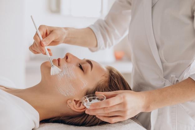 Kosmetolog wykonujący zabiegi na twarz i nakładający maskę na twarz