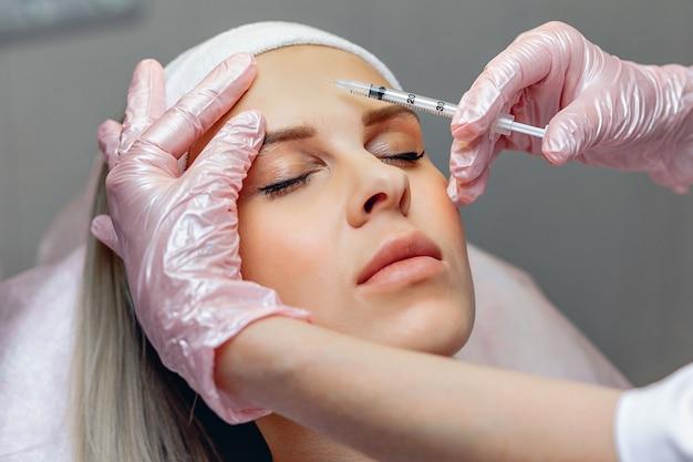 Kosmetolog wykonujący zastrzyki z botoksu w celu odmłodzenia przedniej części twarzy.