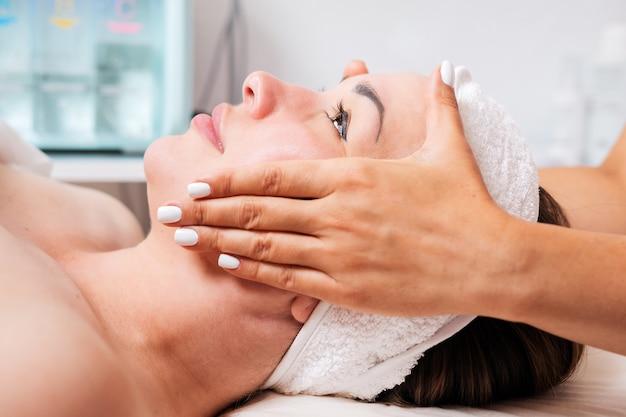 Kosmetolog wykonuje masaż twarzy kobiecie