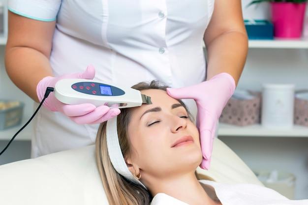 Kosmetolog wykonuje ultradźwiękowe czyszczenie twarzy młodej kobiety