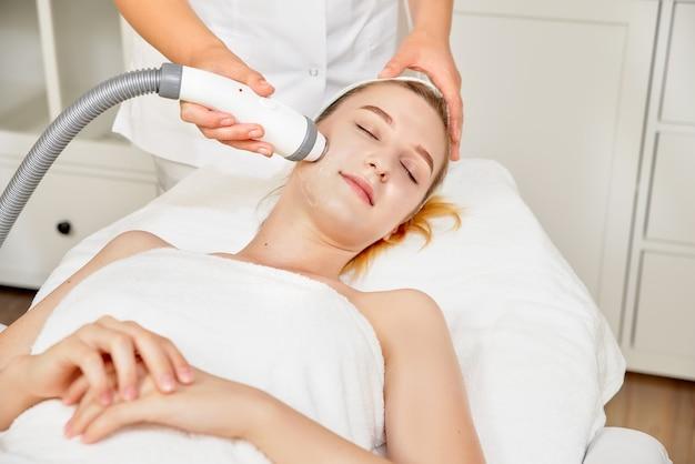 Kosmetolog z bliska wykonujący ultradźwiękowe czyszczenie twarzy jej pacjenta, piękną młodą kobietę. koncepcja oczyszczania i przywracania elastyczności skóry