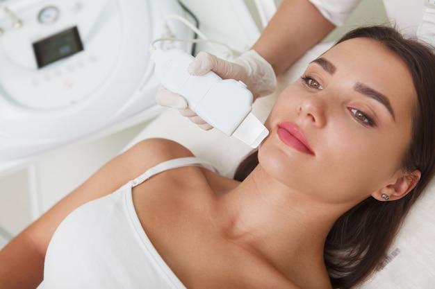 Kosmetolog za pomocą urządzenia ultradźwiękowego na brodzie klientki