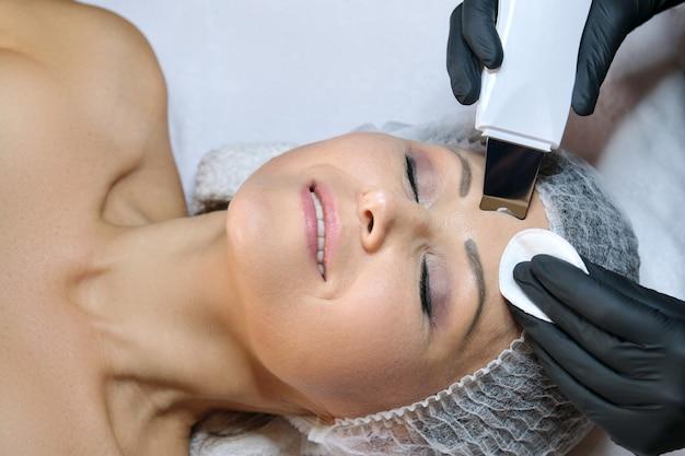 Kosmetologia, dojrzała kobieta otrzymująca czyszczenie twarzy za pomocą urządzenia ultradźwiękowego