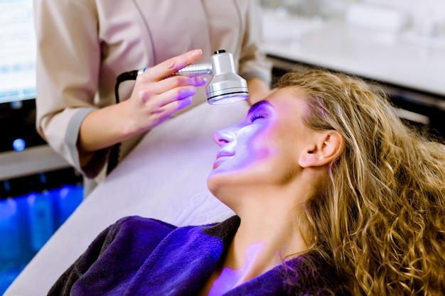 Kosmetologia skóry. kosmetyczka kobieta robi niebieskie światło terapii na twarzy ładnej młodej blond kobiety
