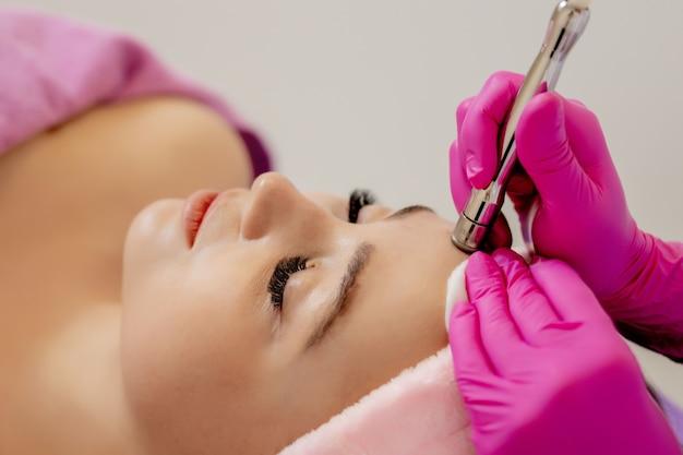 Kosmetologia sprzętowa. kosmetolog wykonujący procedurę ultradźwiękowego czyszczenia twarzy. młoda kobieta coraz ultradźwiękowy peeling w salonie kosmetycznym klinika kosmetyczna. opieka zdrowotna, klinika, kosmetologia