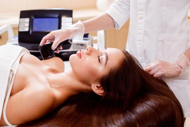 Kosmetologia sprzętowa. masaż próżniowy. piękna młoda kobieta w salonie piękności. z bliska