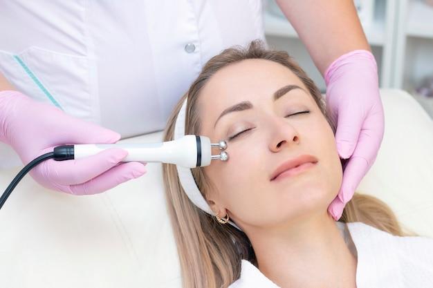 Kosmetologia sprzętowa. zamknij się obraz ślicznej młodej kobiety z zamkniętymi oczami otrzymującej procedurę podnoszenia rf w gabinecie kosmetycznym.