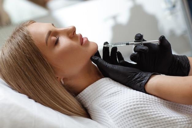 Kosmetyczka dokonywanie zastrzyku w twarz kobiety, zbliżenie. procedura biorewitalizacji. chirurgia plastyczna. salon kosmetyczny