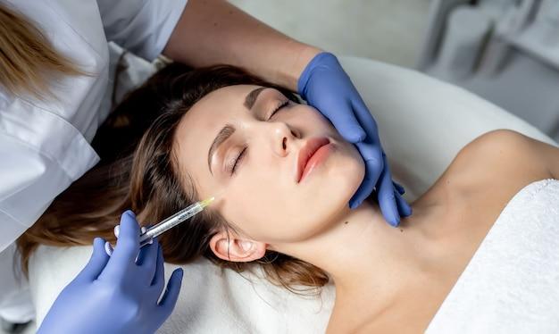 Kosmetyczka dziewczyna robi zastrzyki w usta i twarz pięknej kobiety w klin kosmetyczny