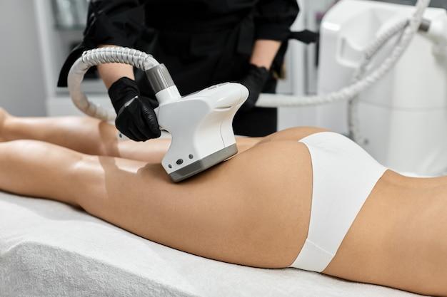 Kosmetyczka lecząca kobiece pośladki masażerem endosfery w gabinecie kosmetycznym