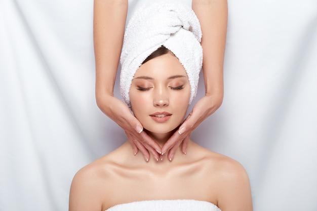 Kosmetyczka masuje kark kobiety w ręczniku kąpielowym i nagimi ramionami