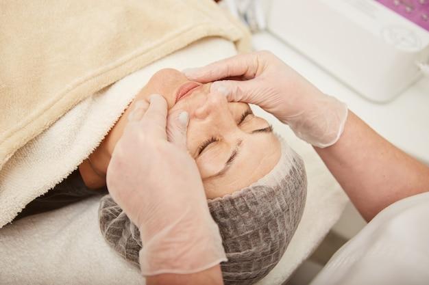 Kosmetyczka masuje twarz kobiety w klinice kosmetologicznej