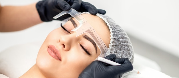 Kosmetyczka mierzy brwi linijką przed tatuowaniem brwi