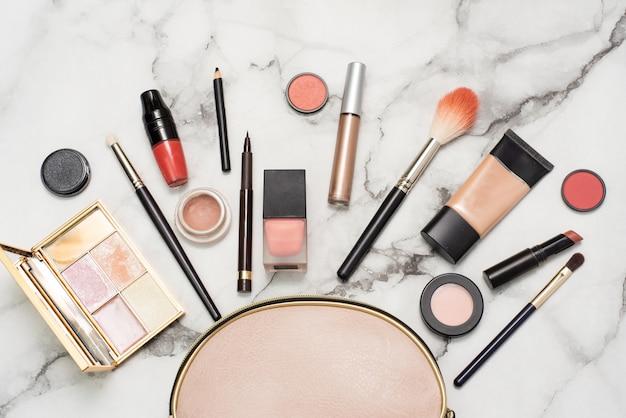 Kosmetyczka na marmurowym tle z pędzlem do makijażu, podkładem tonalnym, szminką, konturówką, różem i cieniem do powiek. koncepcja drogich luksusowych kosmetyków