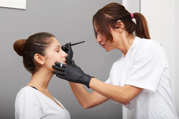 Kosmetyczka nakłada makijaż permanentny na brwi