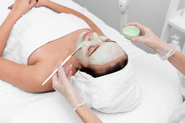 Kosmetyczka nakłada maskę na twarz klienta