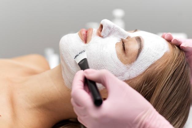 Kosmetyczka nakłada pędzlem białą maseczkę z glinki na twarz kobiety