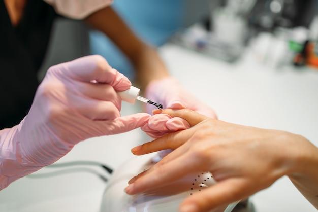 Kosmetyczka nakładająca lakier do paznokci klientce