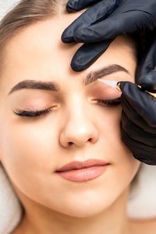 Kosmetyczka nakładająca makijaż permanentny na brwi młodej kobiety specjalnym narzędziem do tatuażu