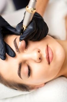 Kosmetyczka nakładająca makijaż permanentny na brwi za pomocą narzędzia do tatuażu