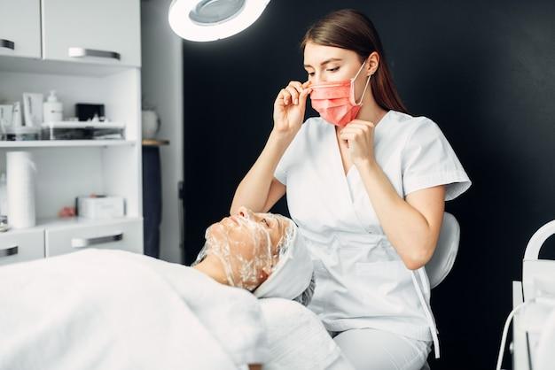 Kosmetyczka obserwuje twarz pacjenta w masce