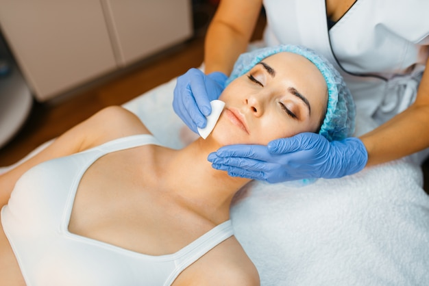 Kosmetyczka oczyszcza skórę twarzy pacjentce.
