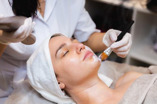 Kosmetyczka pędzelkiem nakłada białą maseczkę nawilżającą na twarz młodej klientki w gabinecie kosmetycznym spa