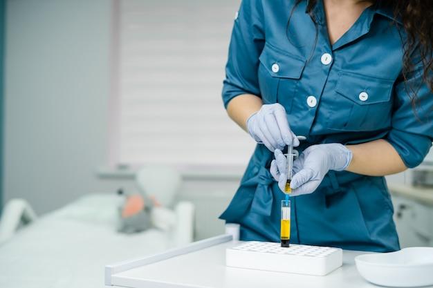 Kosmetyczka pobiera krew w strzykawce z testu w probówce