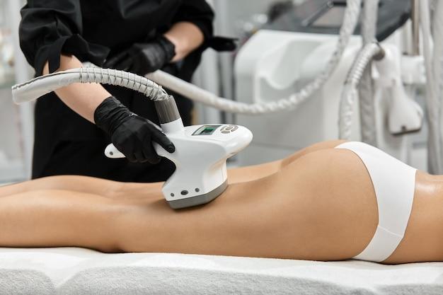Kosmetyczka pracująca na kobiecych nogach z profesjonalnym aparatem endosfery lpg w salonie spa