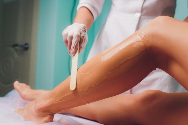 Kosmetyczka przygotowuje się do depilacji i nakłada krem z woskowym patyczkiem na piękne kobiece nogi. salon piękności.