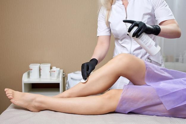 Kosmetyczka przygotowuje się do woskowania kobiecych nóg w centrum spa. przygotowanie do depilacji