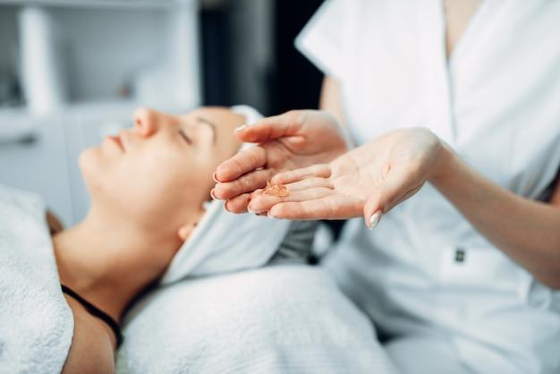 Kosmetyczka ręce kremem przed pacjentką