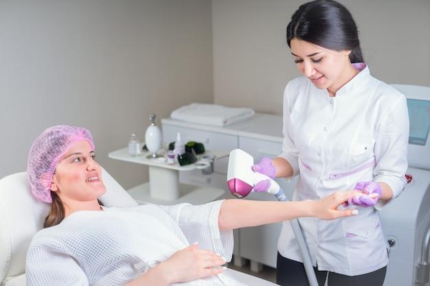 Kosmetyczka robi depilację pięknej kobiecej dłoni w centrum medycznym. kobieta otrzymująca laserowe włosy