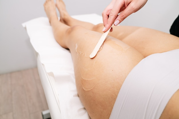 Kosmetyczka robi depilację woskiem kobiecie na udzie