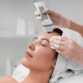 Kosmetyczka robi rutynową pielęgnację twarzy dla klientki