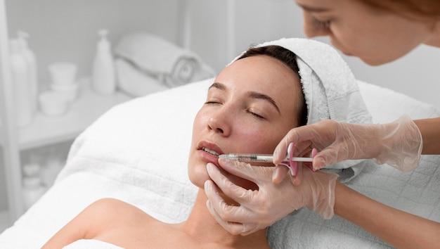 Kosmetyczka robi wypełniacz zastrzyków na klientce