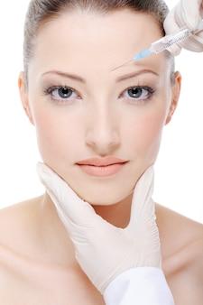 Kosmetyczka robi zastrzyk na młodej kobiecej twarzy
