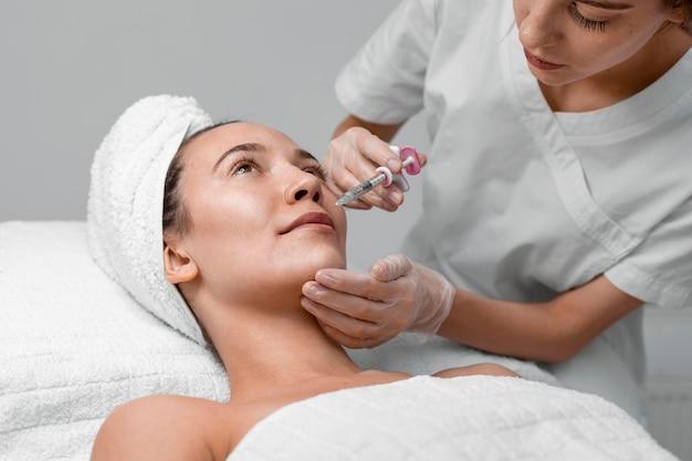 Kosmetyczka robi zastrzyk wypełniacza dla klientki