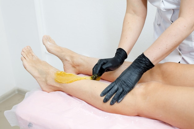 Kosmetyczka stosująca depilację cukrową na nodze, usuwanie włosów dla kobiet