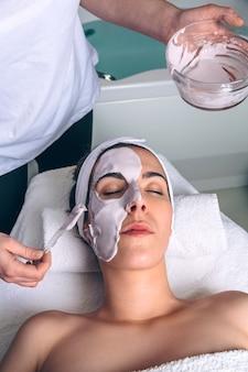 Kosmetyczka stosująca glinianą maskę na twarz młodej kobiecie leżącej z zamkniętymi oczami w spa. koncepcja medycyny, opieki zdrowotnej i urody.