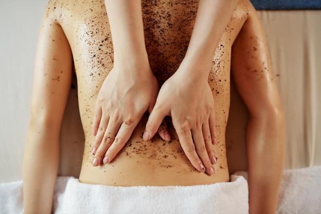 Kosmetyczka stosująca peeling do ciała