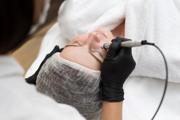 Kosmetyczka-terapeutka wykonuje zabieg laserowy na twarzy młodej kobiety w gabinecie kosmetycznym spa.