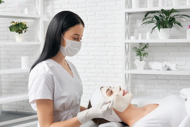 Kosmetyczka trzymając pędzel i robi zabieg dla kobiety