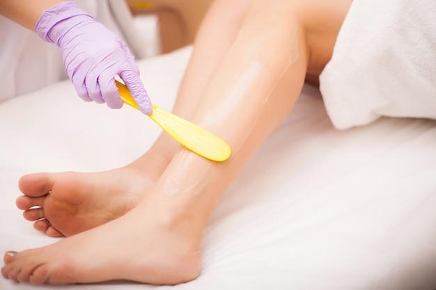 Kosmetyczka usuwa włosy na pięknych kobiecych nogach za pomocą lasera