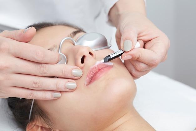 Kosmetyczka usuwanie włosów młodej kobiety za pomocą lasera
