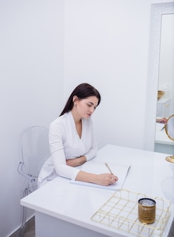 Kosmetyczka w białym mundurze siedzi przy stole i robi notatkę w zeszycie. centrum kosmetologii