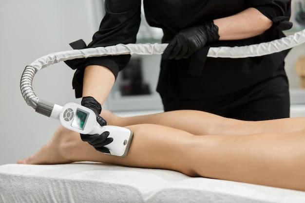 Kosmetyczka w czarnych rękawiczkach robi masaż laeg na ciele kobiety masażerem lpg