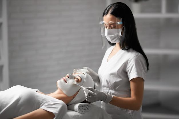 Kosmetyczka w masce ochronnej robi peeling dla pacjenta