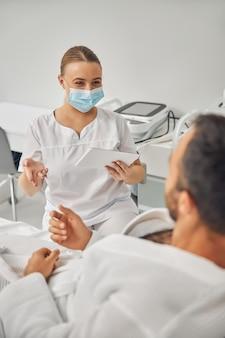 Kosmetyczka w medycznej masce na twarz trzymająca elektroniczny pad pc podczas rozmowy z pacjentem płci męskiej