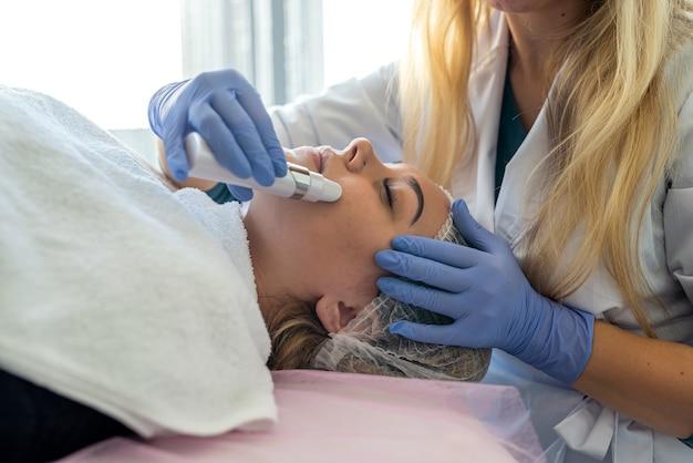 Kosmetyczka w niebieskich rękawiczkach wykonuje zabieg ultradźwiękowego oczyszczania twarzy młodej pacjentce. kosmetologia sprzętowa.
